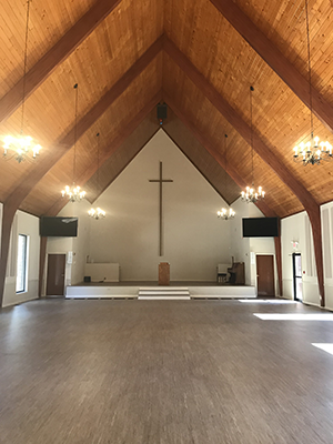Inside a church with a light stained wood ceiling and cross. There is no furniture.