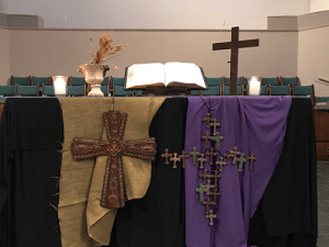 Table covered in a light brown drap and a puple drap each with a woven cross. The table has a bible and cross on top.