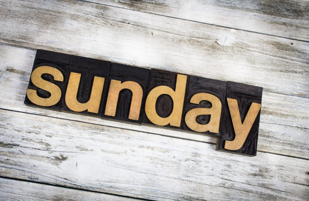 "The word ""Sunday"" written in wooden letterpress type on a white washed old wooden boards background."