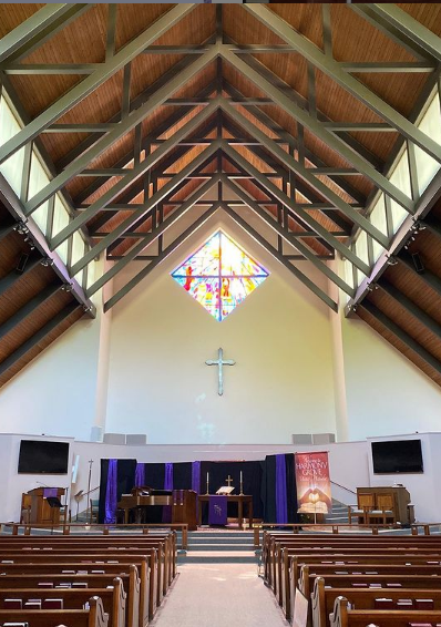 View of sanctuary looking towards the front. The cross and stain glass window are visible.