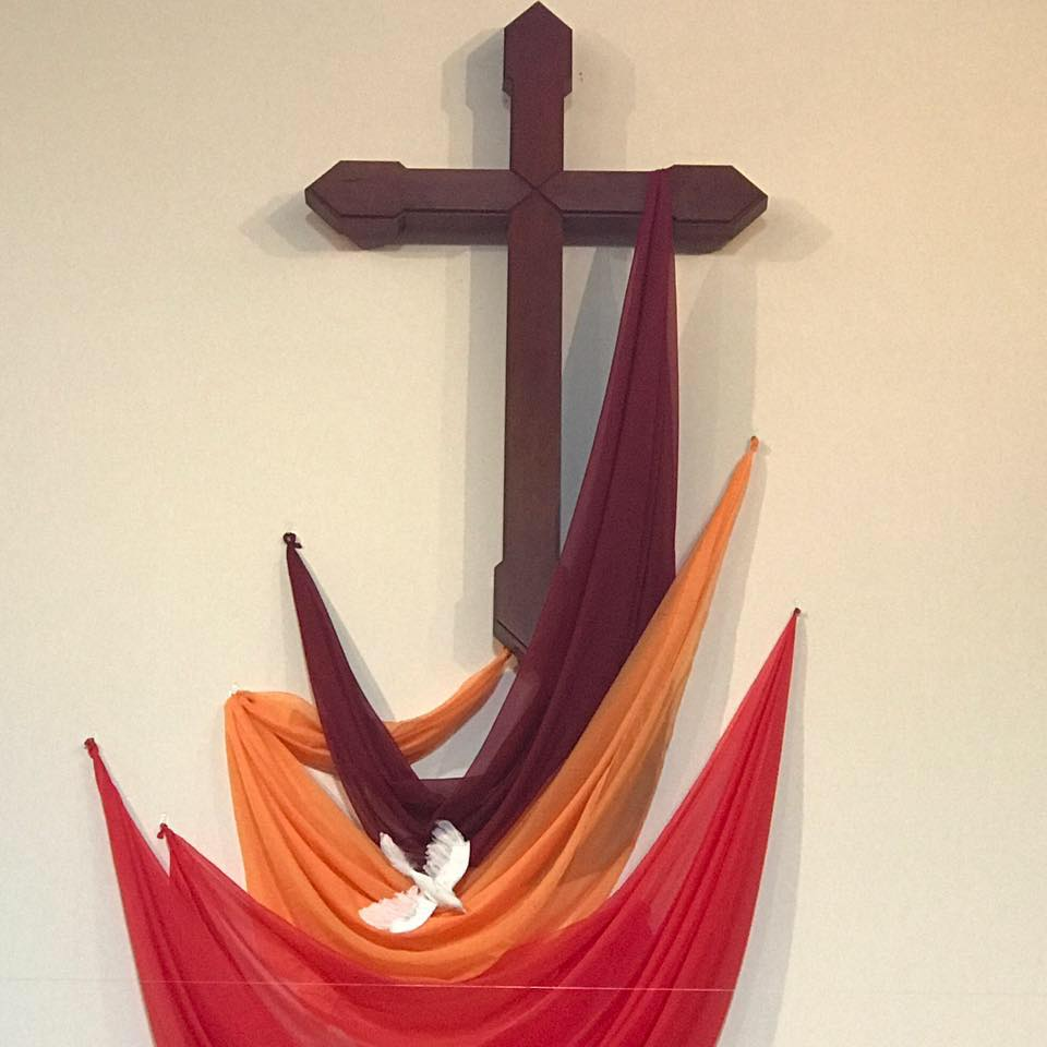Cross with a dove and flames of brown, orange and red.